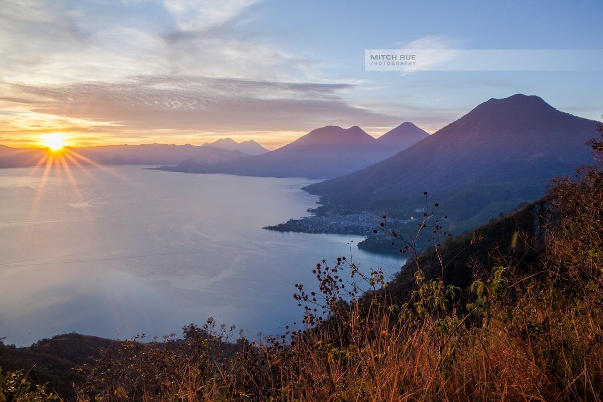 Sonnenaufgang am Lake Atitlan in Guatemala. Die Vulkane werden von warmem Licht angestrahlt.