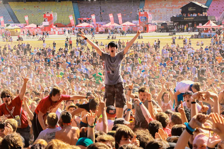 Ein Fan steht jubelnd bei einem OpenAir in der Menge